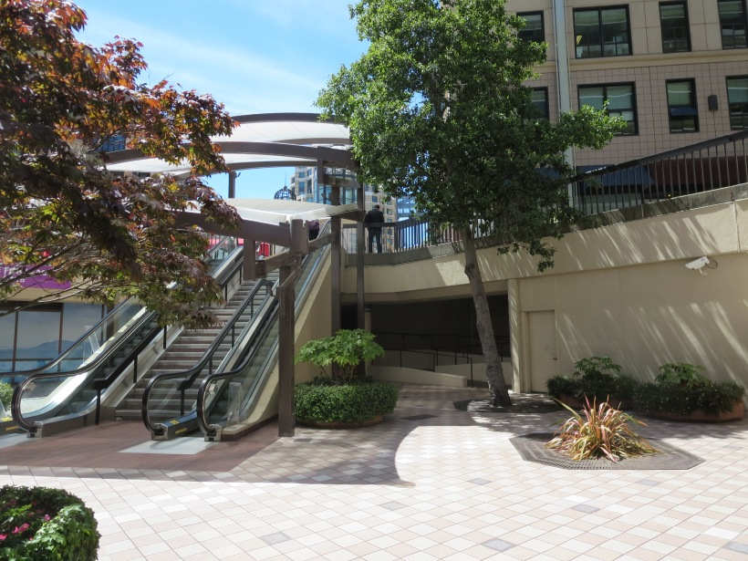 These escalators and steps lead the pedestrian to ground level and the beginning of the main part of the plaza.