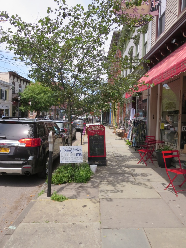 The sidewalks in Saugerties are accentuated with signs, tables and chairs, and goods for sale creating an interesting and varied area to walk.
