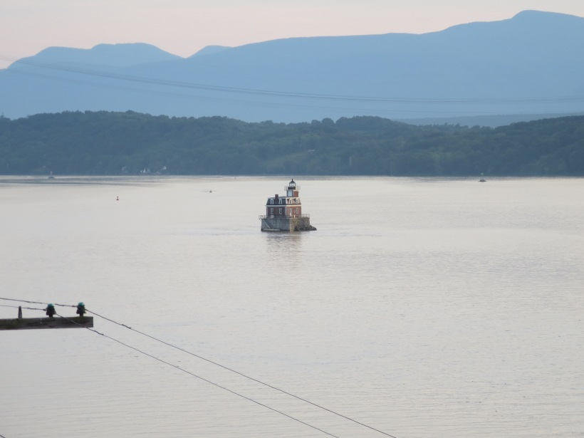 The Hudson Athens Lighthouse sits in the Hudson River with the Catskill Mountains in the background.