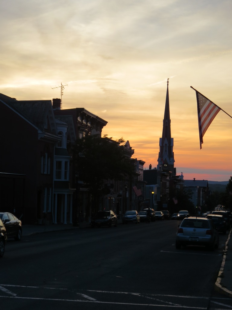 The sun sets over Hudson, NY with the First Presbyterian Church in the background.